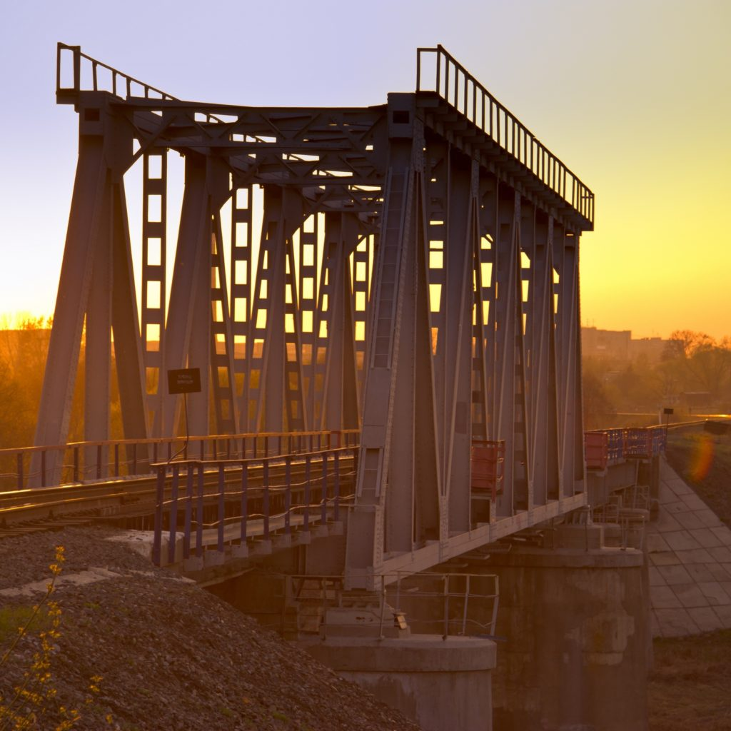Railway bridge over the river at sunset.