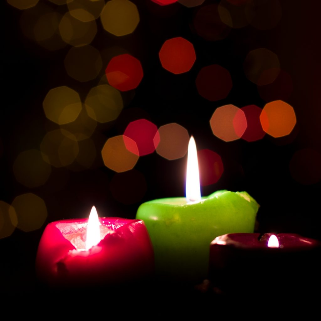 Three candles on a Christmas tree background.