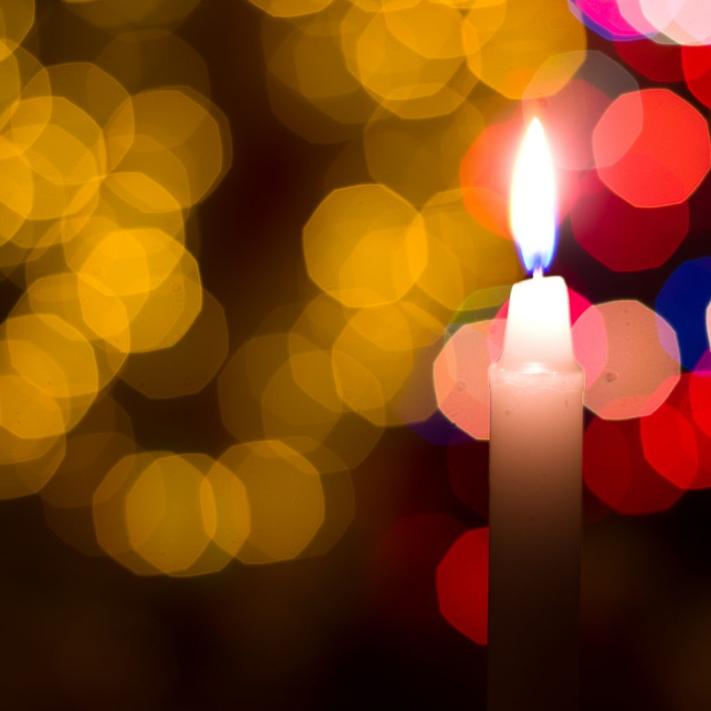 Candle on a Christmas tree background.