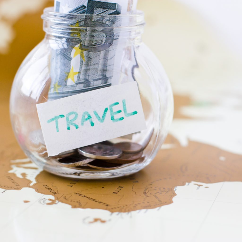 Travel budget – vacation money savings in a glass jar on world m